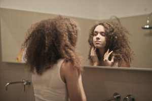 woman-in-white-tank-top-while-looking-herself-at-a-mirror-3811809